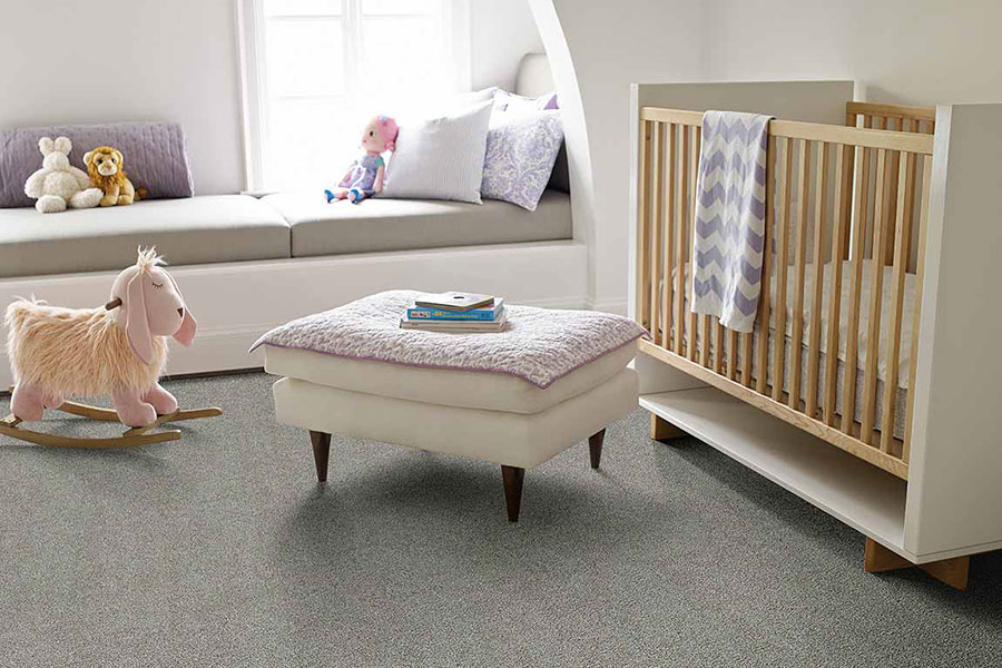 Baby's room with grey carpet and decorated with a modern crib, an ottoman with a pink baby blanket draped over it, a pink baby rocking horse, and purple throw pillows on a window seating area.