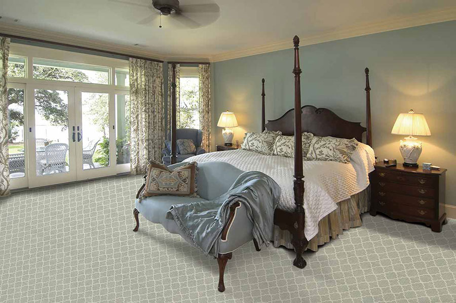 Bedroom furnished with a large four post canopy bed and two dark-stained wood nightstands on with lamps and patterned carpet.