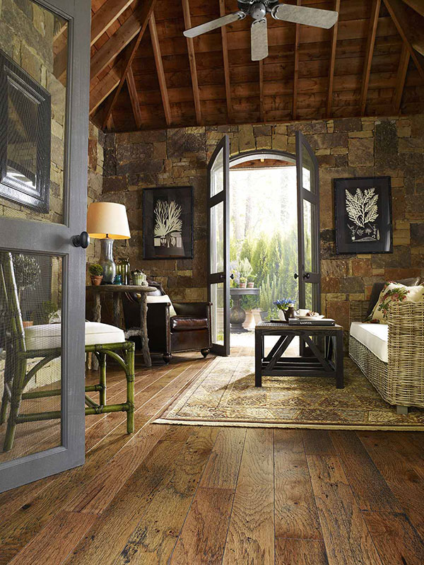 Living room inside a rustic cabin with a wicker couch and area rug on the wood floor.