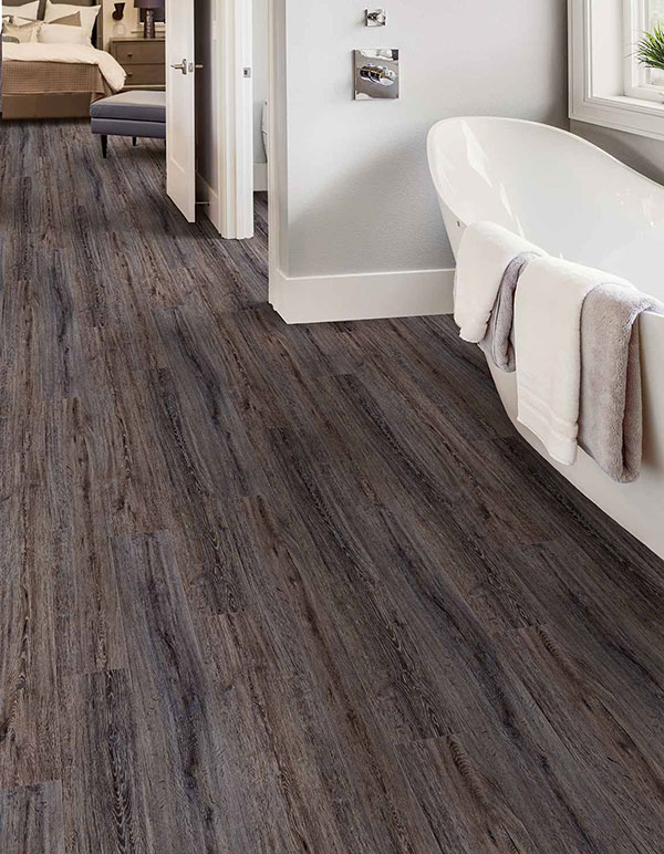 ] Close up image of a trending 2020 floors utilizing luxury vinyl tiles (LVT) and a large white soaking tub.