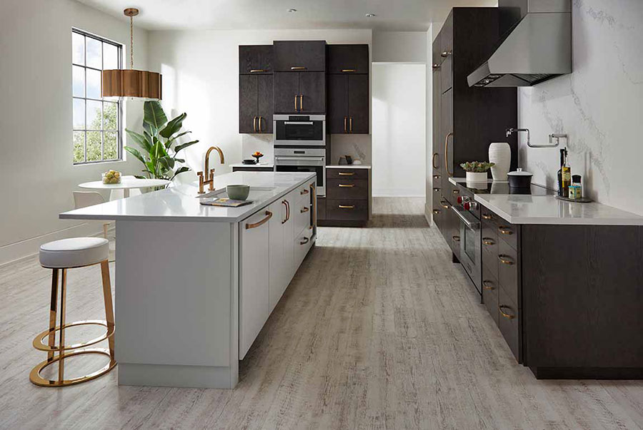 Modern themed kitchen with dark stained cabinets, stainless steel appliances, and grey colored island on luxury vinyl plank flooring.