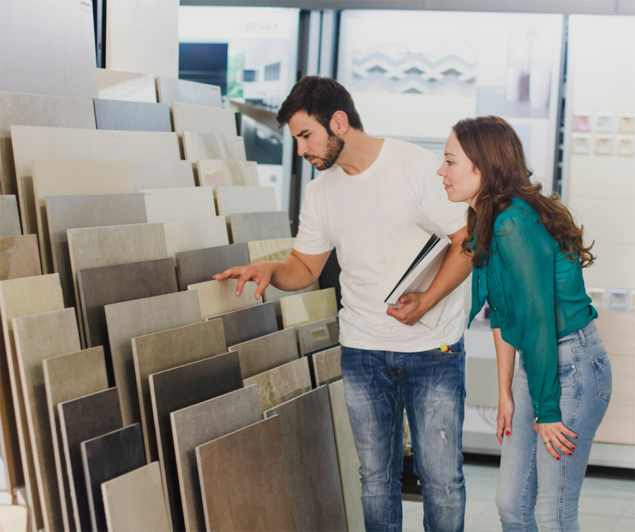 Couple in flooring store looking at samples of ceramic tile in different colours