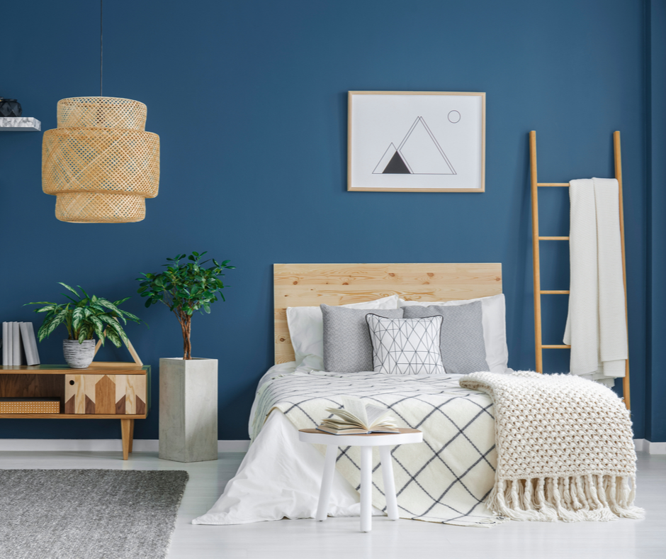 A modern bedroom utilizing 2020 themed colours to include stormy blue walls, grey planters, and a natural wood headboard.