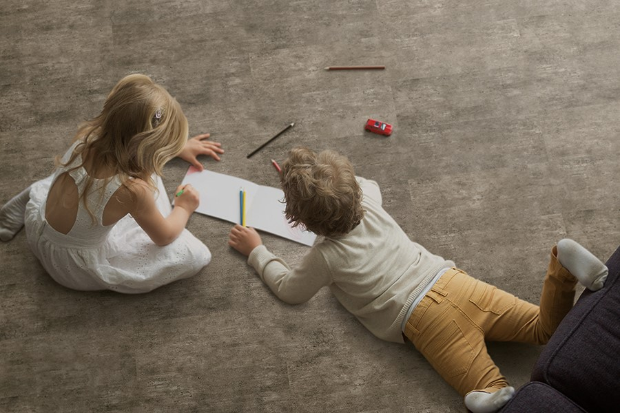 Kids drawing on a piece of paper on a carpet floor