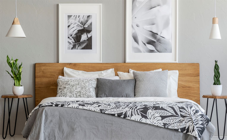 Bedroom utilizing a 2020 neutral color theme that incorporates a grey-toned bedspread, walls, and a natural wood headboard.